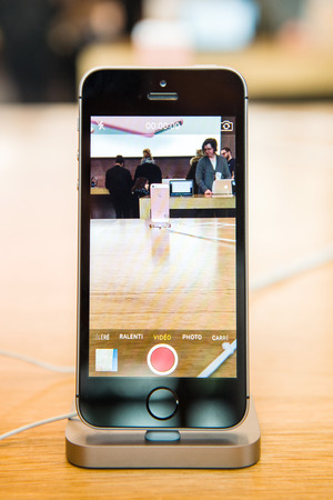 tends: STRASBOURG, FRANCE - APR 9, 2016: New iPhone SE in docking station recording Apple Store with camera app. New Apple iPhone tends to become one of the most popular smart phones in the world.