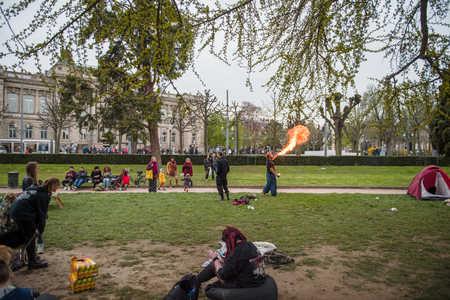 conflictos sociales: STRASBOURG, FRANCE - APR 9, 2016: Fire-eater performing as people join the Nuit Debout or Standing night movement at the Place de la Republique in Strasbourg