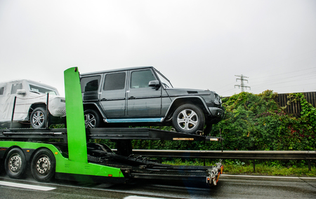transported: HUNGARY - SEPTEMBER 18, 2013: Modern New luxury Mercedes-Benz G-Class SUV cars being transported on a HODLMAYR trailer near Hungarian border. Hodlmayr is an Austrian international transportation company