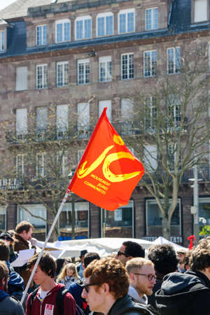 nationwide: STRASBOURG, FRANCE - APR 20, 2016: Young Communist Movement flag at protest of hundreds of people demonstrate as part of nationwide day of protest against proposed labor reforms by Socialist Government