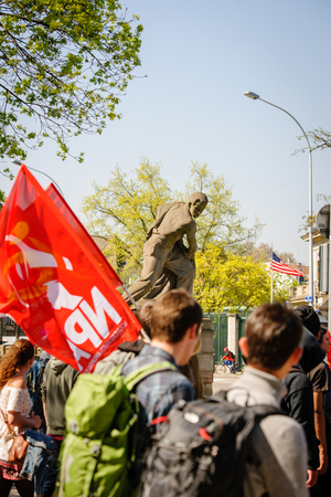 reforms: STRASBOURG, FRANCE - APR 20, 2016: American statue on bridge with hundreds of people demonstrate as part of nationwide day of protest against proposed labor reforms by Socialist Government Editorial