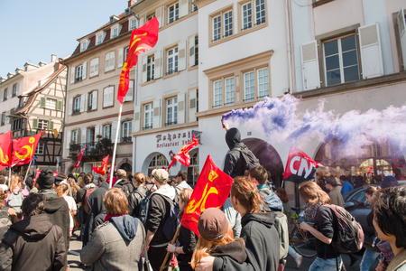 proposed: STRASBOURG, FRANCE - APR 20, 2016: Man holding smoke grenade as hundreds of people demonstrate as part of nationwide day of protest against proposed labor reforms by Socialist Government