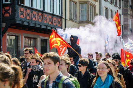 reforms: STRASBOURG, FRANCE - APR 20, 2016:Man holding smoke grenade as hundreds of people demonstrate as part of nationwide day of protest against proposed labor reforms by Socialist Government