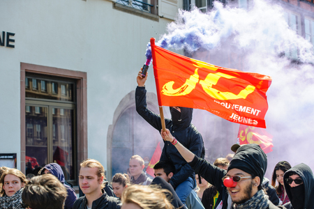 nationwide: STRASBOURG, FRANCE - APR 20, 2016:Man holding smoke grenade as hundreds of people demonstrate as part of nationwide day of protest against proposed labor reforms by Socialist Government