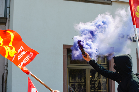 socialist: STRASBOURG, FRANCE - APR 20, 2016:Man holding smoke grenade as hundreds of people demonstrate as part of nationwide day of protest against proposed labor reforms by Socialist Government