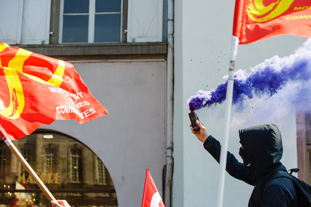 proposed: STRASBOURG, FRANCE - APR 20, 2016:Man holding smoke grenade as hundreds of people demonstrate as part of nationwide day of protest against proposed labor reforms by Socialist Government