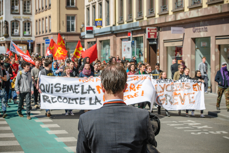 reforms: STRASBOURG, FRANCE - APR 20, 2016: Man looking at protest as hundreds of people demonstrate as part of nationwide day of protest against proposed labor reforms by Socialist Government Editorial
