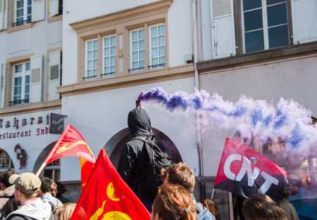 socialist: STRASBOURG, FRANCE - APR 20, 2016: Man holding smoke grenade as hundreds of people demonstrate as part of nationwide day of protest against proposed labor reforms by Socialist Government