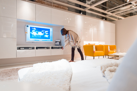PARIS, FRANCE - APR 12, 2016: Woman choosing modern living room furniture and TV sets in the modern IKEA shopping furniture mall in Paris