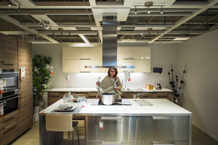 apartment market: PARIS, FRANCE - APR 12, 2016: Woman choosing modern kitchen furniture and kitchen appliances in the modern IKEA shopping furniture mall in Paris
