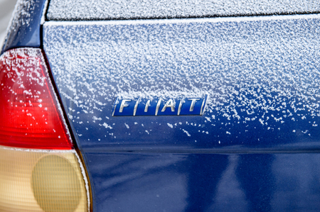 automaker: PARIS, FRANCE - JAN 20, 2016: FIAT logotype covered with snow flakes. FIAT is an Italian automaker which produces Fiat branded cars, and is part of Fiat Chrysler Automobiles