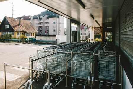 pushcart: Rows of shopping carts in supermarket or hypermarket parking waiting for customers with houses in the bacground