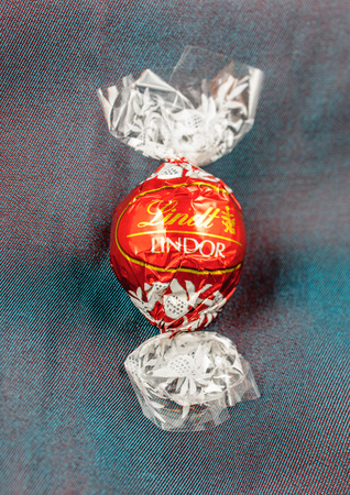 KILCHBERG, SWITZERLAND - MARCH 20, 2014: Lindt Lindor chocolate truffle on a chameleon luxury silk background. Lindt is one one of the lastgest luxury chocolate and confectionery company worldwide with more than 30 factories worldwide