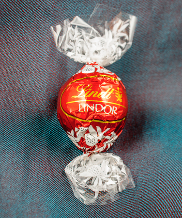 lindt: KILCHBERG, SWITZERLAND - MARCH 20, 2014: Lindt Lindor chocolate truffle on a chameleon luxury silk background. Lindt is one one of the lastgest luxury chocolate and confectionery company worldwide with more than 30 factories worldwide