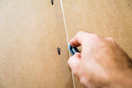 box cutter: Caucasian man cutting a cardboard box with sharp steel box cutter knife  while installing new furniture