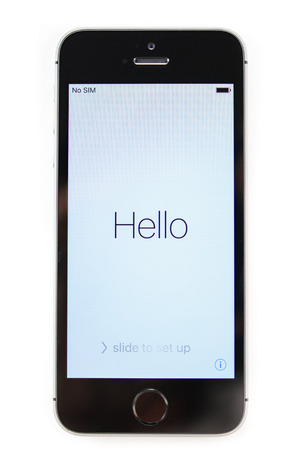 retina display: PARIS, FRANCE - APR 21, 2016: First start of the new iPhone SE with Hello message on screen - the new phone combines the updated processor, 4K rear camera, touch id, retina display