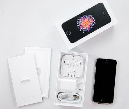 combining: PARIS, FRANCE - APR 21, 2016: Unboxing of the new Apple iPhone SE combining the updated processor, 4K rear camera, touch id, retina display