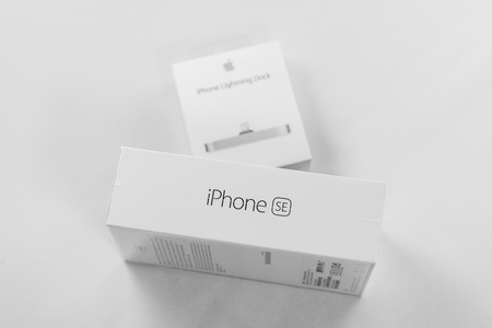retina display: PARIS, FRANCE - APR 21, 2016: Packaging box of the new Apple iPhone SE combining the updated processor, 4K rear camera, touch id, retina display and new Docking Station for iphone