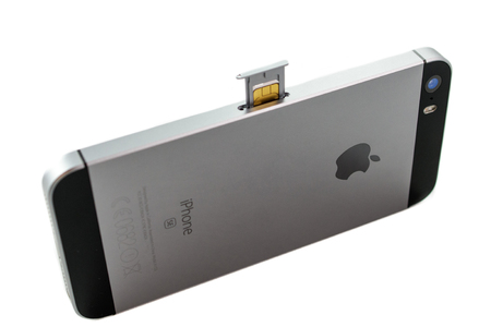 combining: PARIS, FRANCE - APR 21, 2016: Instalation of the new SIM card in the new Apple iPhone SE combining the updated processor, 4K rear camera, touch id, retina display Editorial