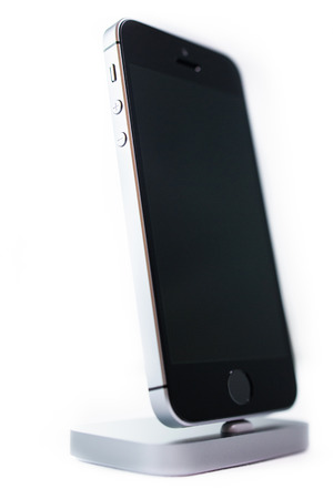 retina display: PARIS, FRANCE - APR 21, 2016: Front view of the new Apple iPhone SE in docking station combining the updated processor, 4K rear camera, touch id, retina display