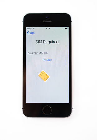 display retina: PARIS, FRANCE - APR 21, 2016: First start of the new iPhone SE with SIm required message on screen - the new phone combines the updated processor, 4K rear camera, touch id, retina display