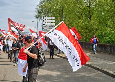 frei: STRASBOURG, FRANCE - APR 30, 2016: Man with red flag on closed street as crowd protest against government regional reform for the fusion of the Alsace region with Lorraine and Champagne-Ardenne Editorial