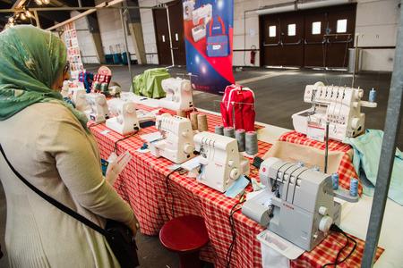 maquinas de coser: Estrasburgo, Francia - ABR 24 de, 2016: mujer musulmana mirando a las máquinas de coser en el tradicional mercado cubierto de textiles con varios colores y texturas diferentes