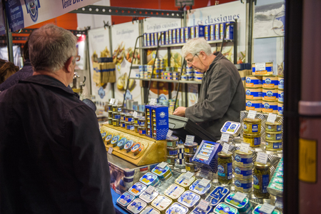preserves: STRASBOURG, FRANCE - APR 24, 2016: People buying traditional French fish preserves from fisherman at the traditional french cusine covered market