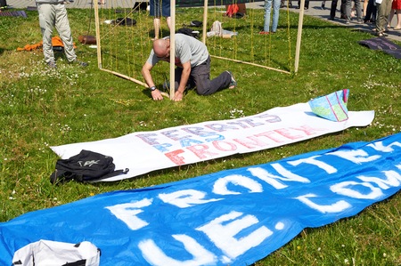 european parliament: STRASBOURG, FRANCE -MAy 8, 2016: Open Doors day, Closed doors at borders - protest in front of the European Parliament during EU migrant policy - man preparing placards