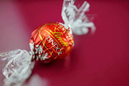 lindt: KILCHBERG, SWITZERLAND - MARCH 20, 2014: Tasty Lindt Lindor chocolate truffle on a red luxury silk background. Lindt is one one of the lastgest luxury chocolate and confectionery company worldwide with more than 30 factories worldwide Editorial