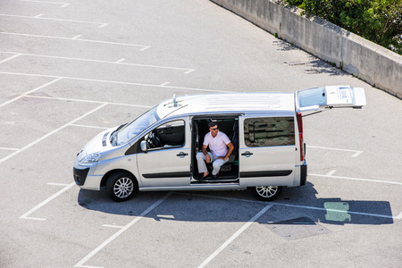 int: MARSEILLE, FRANCE - JUL 18, 2014: Elevated view of a man sitting int the empty light commercial vehicle taxi car (Peugeot Expert) Editorial