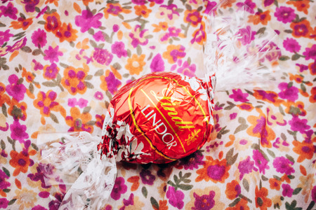 KILCHBERG, SWITZERLAND - MARCH 20, 2014: Beautiful Lindt Lindor chocolate truffle on a red luxury silk background. Lindt is one one of the lastgest luxury chocolate and confectionery company worldwide with more than 30 factories worldwide Editorial