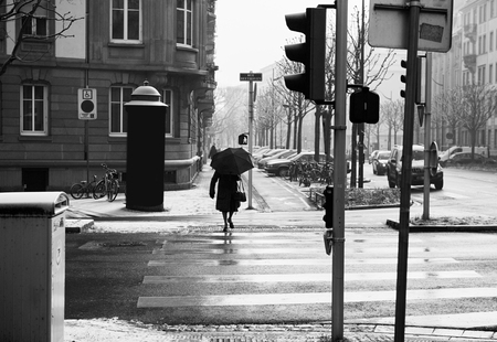 crossing street: Silhouette of woman crossing street with umbrella on a snowy day