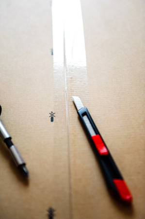 box cutter: Cutter and screwdriver on box of furniture just above the scotch protection tape Stock Photo