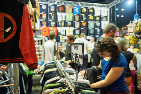 STRASBOURG, FRANCE - MAY 8, 2015: Woman buying t-shirt, souvenirs and cult objects at the open market Digital Game Manga Show Editorial