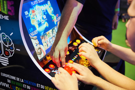 STRASBOURG, FRANCE - MAY 8, 2015: Man playing arcade game at the open market Digital Game Manga Show