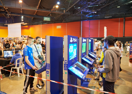 wii: STRASBOURG, FRANCE - MAY 8, 2015: Kids and adults playing PS 4 game consoles at the open market Digital Game Manga Show Editorial