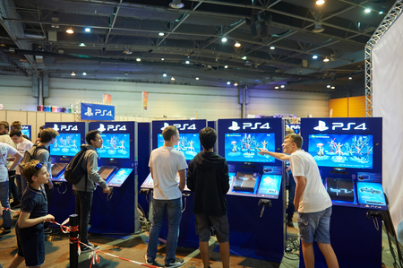 STRASBOURG, FRANCE - MAY 8, 2015: Kids and adults playing PS 4 game consoles at the open market Digital Game Manga Show Editorial