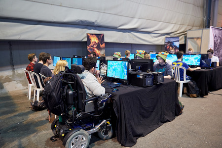 STRASBOURG, FRANCE - MAY 8, 2015: man in wheelchair competing in computer tournament at the open market Digital Game Manga Show Editorial