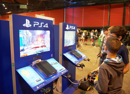 ps: STRASBOURG, FRANCE - MAY 8, 2015: Two friends playing PS 4 game consoles at the open market Digital Game Manga Show