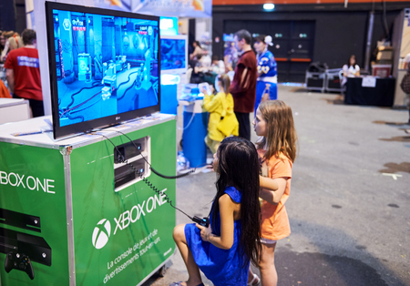 playing the market: STRASBOURG, FRANCE - MAY 8, 2015: Two young girls playing XBOX One game console at the open market Digital Game Manga Show