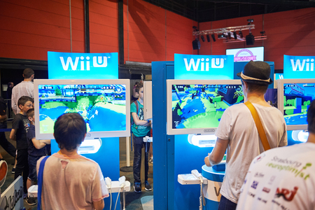 roleplaying: STRASBOURG, FRANCE - MAY 8, 2015: Kids and adults playing WII U game consoles at the open market Digital Game Manga Show Editorial