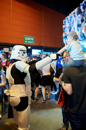 roleplaying: STRASBOURG, FRANCE - MAY 8, 2016: Darth Vader shaking hand with little fan boy at the open market Digital Game Manga Show