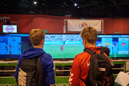 xbox: STRASBOURG, FRANCE - MAY 8, 2015: Two young brothersplaying XBOX One game console at the open market Digital Game Manga Show