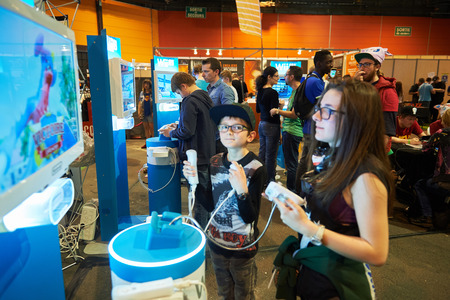 ps: STRASBOURG, FRANCE - MAY 8, 2015: Sister and brother playing PS 4 game consoles at the open market Digital Game Manga Show