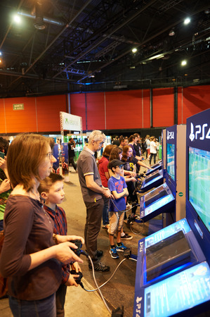 ps: STRASBOURG, FRANCE - MAY 8, 2015: Mother and son playing PS 4 game consoles at the open market Digital Game Manga Show