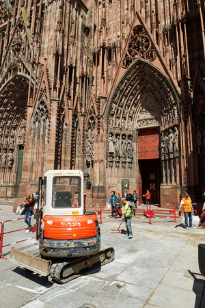 strasbourg: STRASBOURG, FRANCe - MAY 04, 2016: Red Kubota tractor arranging granite pavement sones in from of Strasbourg Cathedral