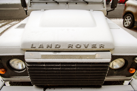 famous industries: PARIS, FRANCE - JAn 20, 2016: Front view of a Land Rover all terrain vehicle car coverd with snow on a winter morning