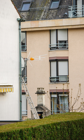digital television: Digital Television TV antenna instalation with ladder over a wall Editorial
