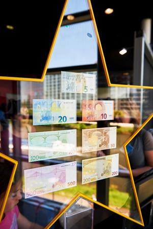 billets euros: STRASBOURG, FRANCE - 8 mai 2016: Foule admirant toutes les notes Euro avec un beau reflet de la fenêtre et du Parlement européen dans les étoiles en les tenant